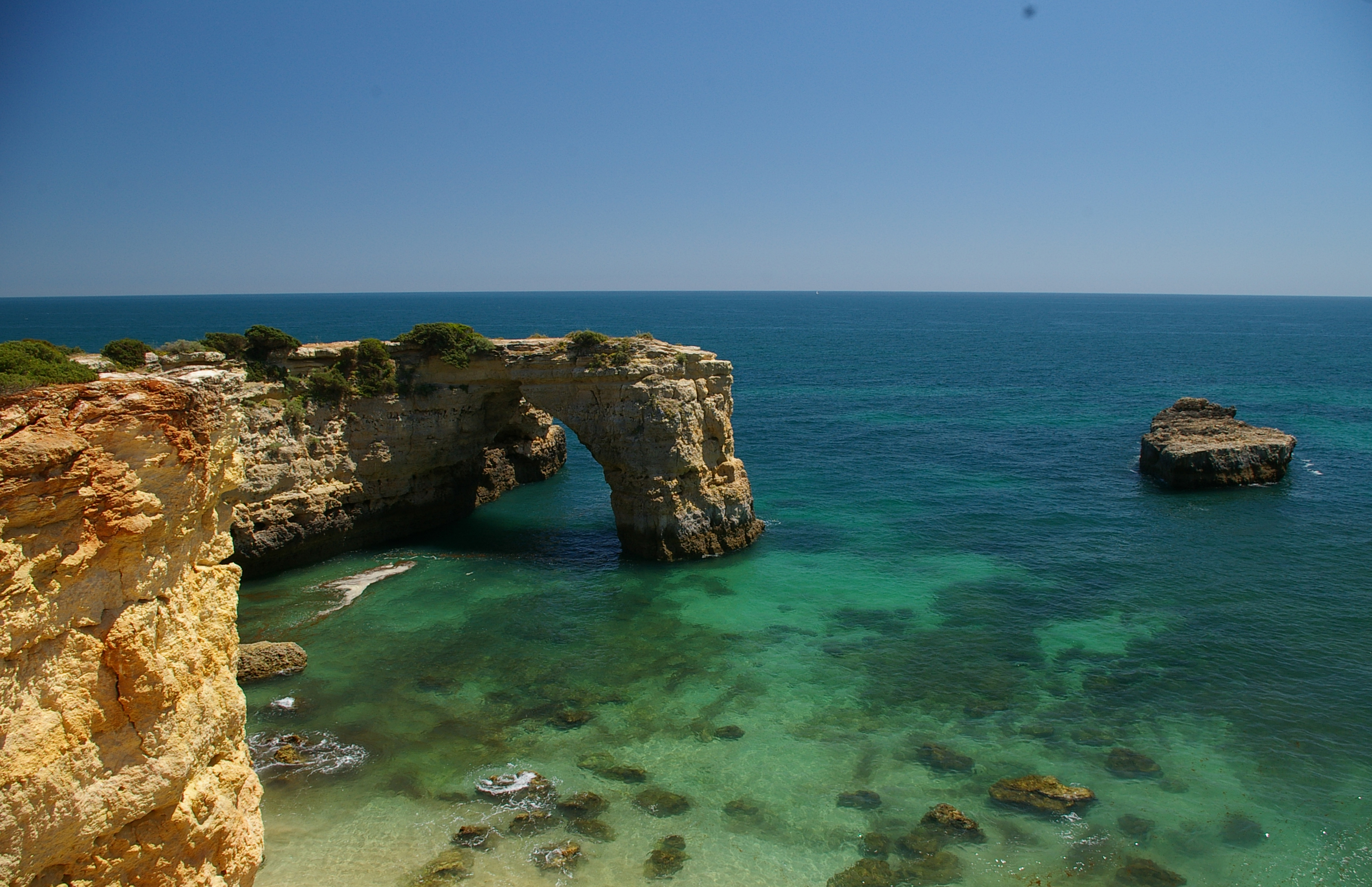 View of the atlantic ocean looking north over the stone arch at Albandeira beach Algarve Portugal
